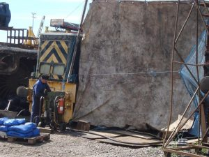 Paul West feeding the shotblasting unit with angular grit granules. Kev is in the tent blasting away at the rear dragbox